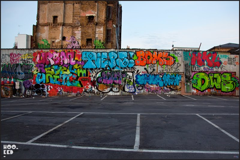 Graffiti covered wall in Sclater Street Car park East London.