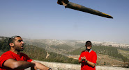 Israeli Protester throws remains of a Rocket