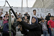 A Palestinian woman shoots in the air during a march by militants from the Al Aqsa Martyrs' Brigade