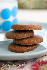 Vegan gluten free gingersnaps in a stack with a glass of cold coconut milk