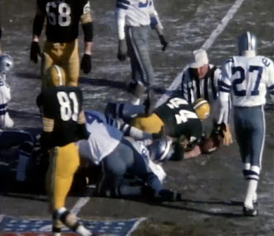 Running back Donny Anderson is stopped after a three-yard gain. Referee  Norm Schachter grabs the ball for the official placement. 553b16317