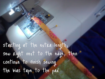 A sewing machine sewing the bias tape to the hot pad.