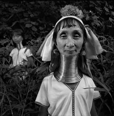 A Karen Paduang Long Neck woman stands with her child in a forest near the border between Burma and Thailand in Southeast Asia. (National Geographic)