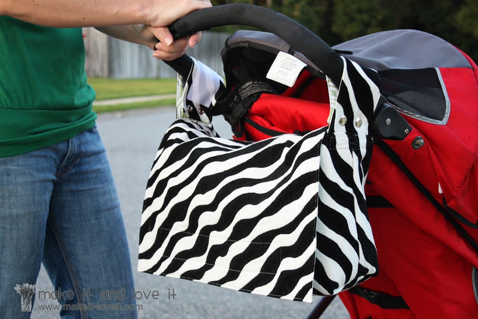 Bag With 2 Snap On Straps Each Side Holding The Up High And Out Of Way It Also Keeps From Slipping Off Stroller Handle S