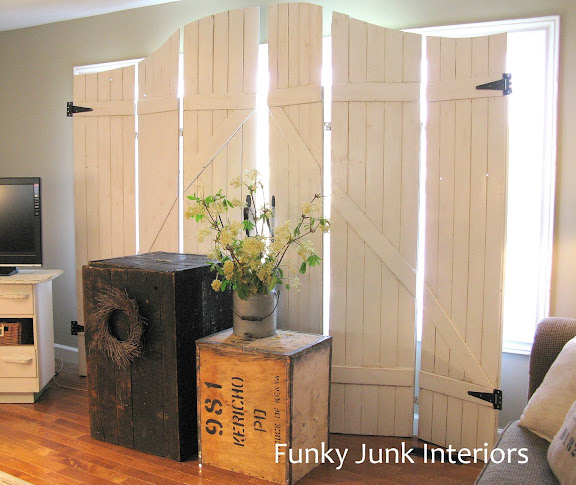 Learn how to easily build your own wooden gate window screens on a room divider with plank wood! Perfect for pet households and they resemble gates or barn doors! Click to full tutorial.