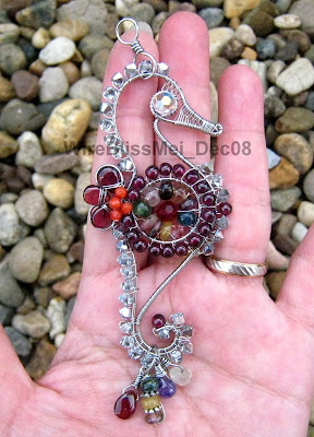 holding the Wire Wrapped Seahorse Pendant with multiple colorful gemstones