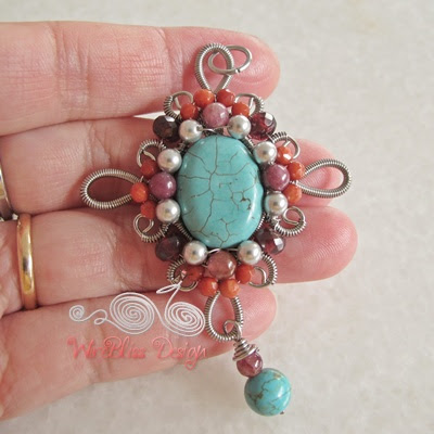 Wire wrapped pendant with turquoise center piece surrounded by smaller gems