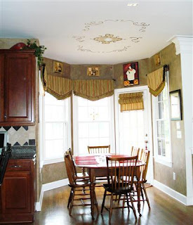 Breakfast room with gorgeous view to rear yard features artistic stenciling on the ceiling above the table area and decorator window dressings