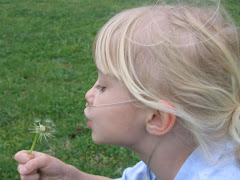 Julia blowing dandelions in the yard