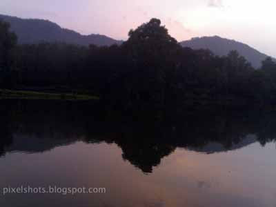 arattu kadavu in chalakkudy river,evening red tinted sky reflecting in the calm river water,photographed from the bank of chalakudy river in kerala