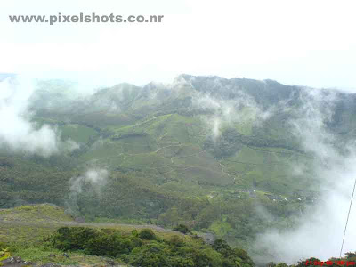 mist in munnar,mountain valleys getting covered in mist,moonar hill station photos,landscape photograph from munnar showing mist moving over mountains of munnar hillstation kerala