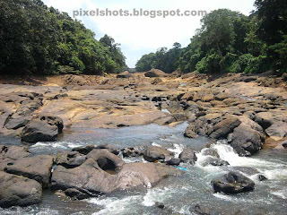 kallada river stream near ottakkal lookout point of thenmala, river photographed when parappar dam is closed in river upstream, river rocks and small stream of water