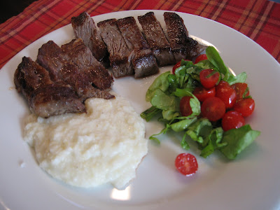 Rib-eye steak, grits, cherry tomatoes and butter lettuce salad