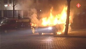 Burning car in front of police station