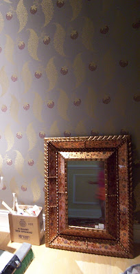 The metallic gold pattern will add sparkle to this small space; like many powder rooms, it has no natural light.