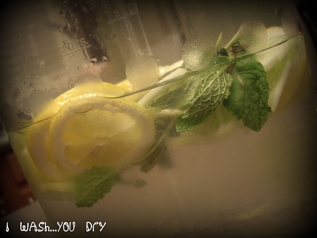 A close up of a container of water with lemons and other things added.