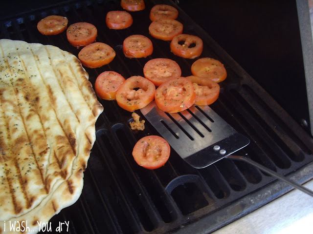 A spatula removing grilled tomato slices.