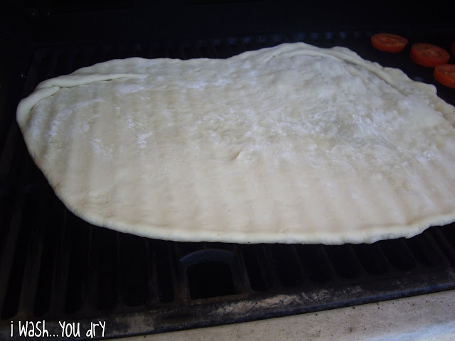 Rolled out pizza dough on a grill.