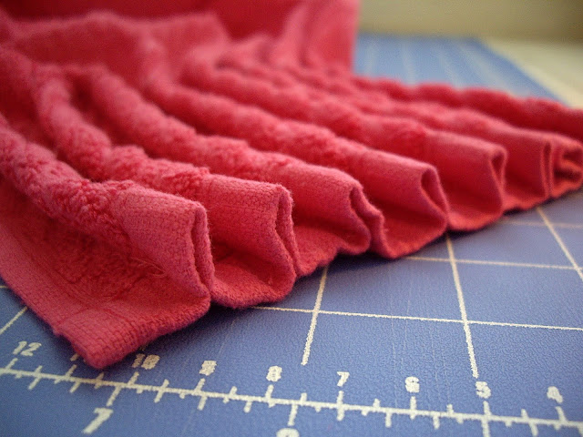 A close up of many pleats on the top of a dishtowel.