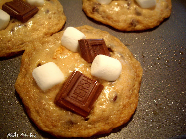A freshly baked cookie on a pan topped with a few marshmallows and a two halves of a chocolate candy bar.