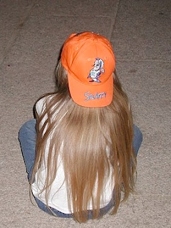 young girl with backwards orange baseball hat