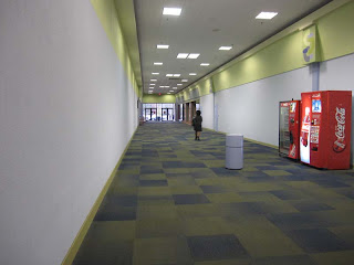 Sky City  Retail History  Gadsden Mall  Gadsden  AL A look along the back right entrance corridor  which features a lot of wall  with the sign of stores in the background  The problem is that these aren t