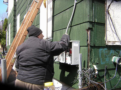 Carmen the Electrician, pulling riser cable through the meter box