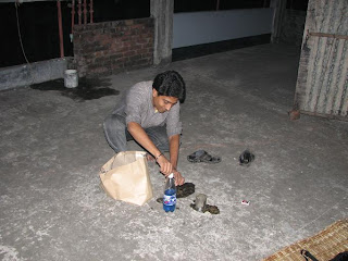 Razib is preparing the torch with sand and kerosene
