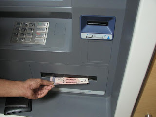 Taking money from ATM booth