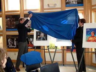 Charles Trautman, izq, director ejecutivo del Ithaca Sciencenter, y Patrick Fish, fundador de la Sagan Appreciation Society con sede en Ithaca, descubren los diseños de la estampa conmemorativa el 11 de febrero.