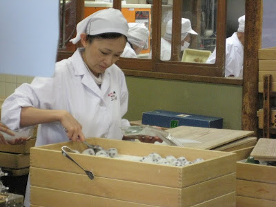 A worker grabbing fresh mochi from a tray