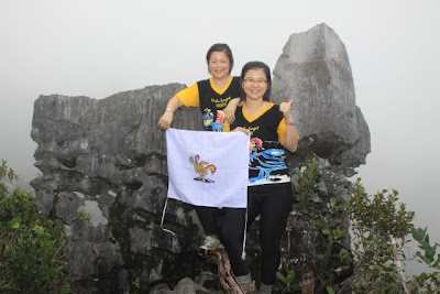 Amelia and Guat Ling displaying HLH4 logo at the view point of the Mulu Pinnacles