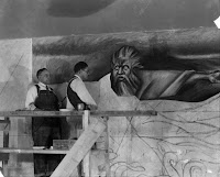 A photograph of two men examining an unfinished mural.