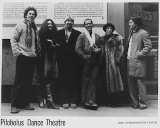 "A black and white photograph of six figures in heavy coats lined up on a sidewalk, captioned ""Pilobolus Dance Theatre."""