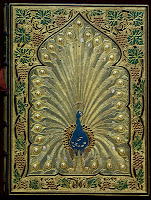 A photograph of an elaborate cover book featuring a peacock surrounded by a border of grapevines. The binding appears to be set mostly in gold with pearls in the peacock's feathers.