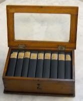 A photograph of nine miniature books in an open wooden case with a glass top.