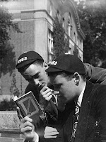 A photograph of two men looking at a book together. They are both wearing caps with the year 1952 on them.