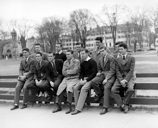 A group of men photographed leaning against a fence.