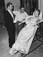 A photograph of Ingrid Bergman leaning back and laughing with two men.