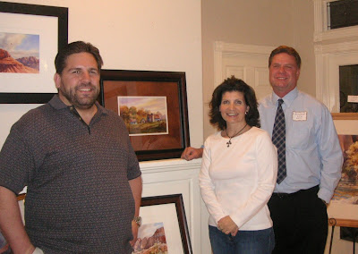 Collectors Nick and Christina Leventis with artist Roland Lee after purchasing his painting of a Vermont Barn