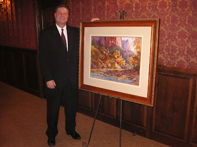 Roland Lee standing by painting which raised $4800.00 for college scholarships