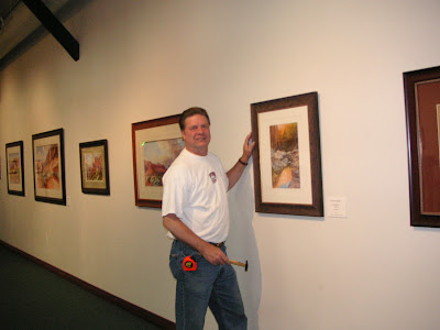 Artist Roland Lee helps hang his one person show at the St. George Art Museum