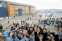 fotografía de un grupo de estudiantes, al fondo se ve el edificio de un establecimiento ewscolar