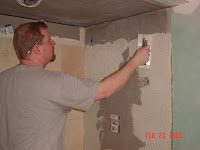 picture of man tiling shower