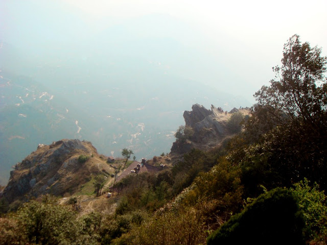 Mukteshwar Dham Temple is on the peak and hence offers great panoramic views of and around Mukteshwar town. On one side you see a deep valley around Chauli ki Gaali and on another side you see green forests with snow peaked mountains in the background. Above photograph is clicked from the hill top where Mukteshwar Dham is located and shows Chauli ki Gali with deep valley below it.