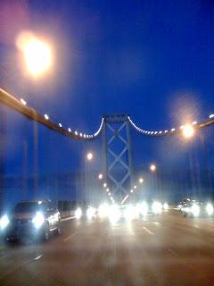 evening photograph of San Francisco Bay Bridge through a dirty or wet car window, photograph by A.E. Graves
