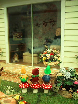 One-twelfth scale miniature scene of a man inside a house with a beer in his hand watching a football match on TV. Outside the ranch sliders in the garden, three gnomes are lined up sitting on mushrooms, watching the match through the glass.