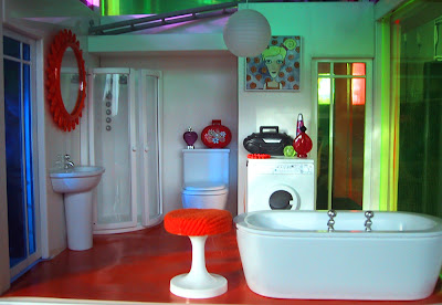 Modern miniature dolls' house bathroom in orange and white.