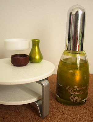 Modern dolls' house miniature coffee table, displaying two bowls and a green vase. On the floor next to it is a full-sized bottle of nail varnish.