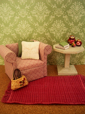 Modern dolls' house miniature scene with green and cream patterned walls, a pink and white armchair and white side table on a pink woven floor rug.